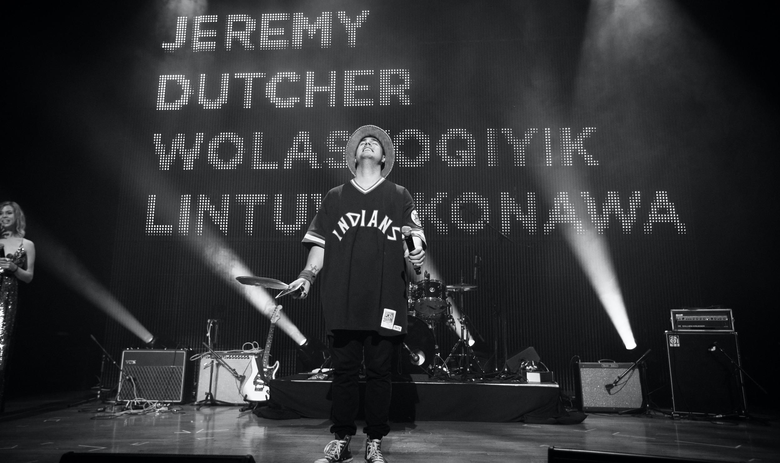 """A  black and white photo of a man standing on stage wearing a hat. In his left hand he holds a microphone. In his right hand, he holds an iPhone and a feather. Behind him are the words written in large letters """"Jeremy Dutcher Wolaskoqiyik Lintuwakonawa."""""""