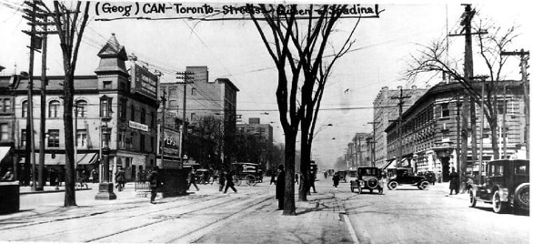"A black and white photograph showing a street scene. At the top of the photograph has been written ""(Geog)- CAN-Toronto-Streets-Queen-Spadina"". The photo reflects the 1920s in Toronto. The camera looks north along a bustling road that is divided with a line of trees down the middle. Old-fashioned cars drive along it and are parked by the side of the road."