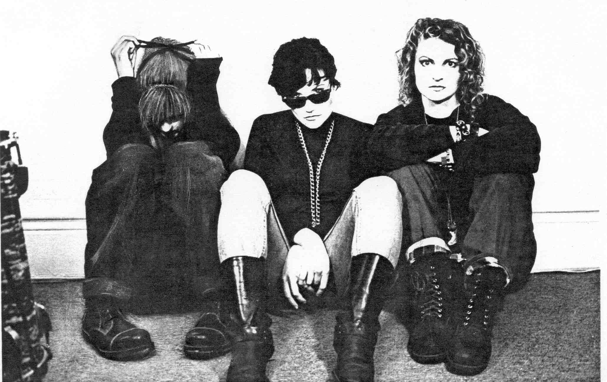 A black and white photo of three women seated against a wall. The woman on the left hand side has her head down and is playing with a ribbon in her hair. The woman in the middle wears sunglasses and looks at the camera. The woman on the right has her arms crossed and resting on her knees.