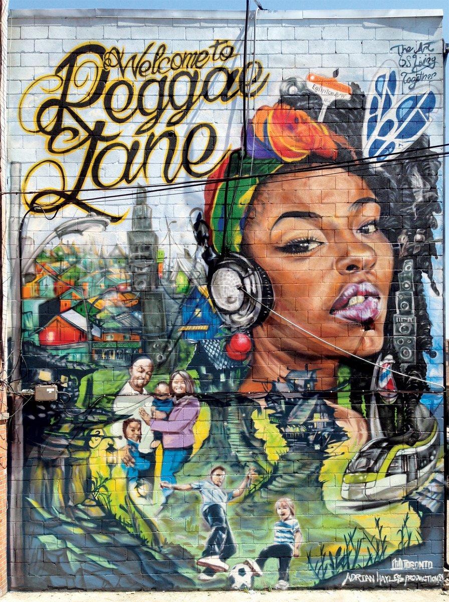 Photo d'une grande murale de graffitis en couleur sur un mur extérieur. Dans la partie supérieure gauche sont inscrits les mots «Welcome to Reggae Lane» (Bienvenue à l'Allée du reggae). La partie droite de la fresque présente une femme portant un casque d'écoute et un foulard coloré. Au bas de la fresque, on voit une scène de rue avec diverses scènes de personnes et d'enfants en train de jouer.