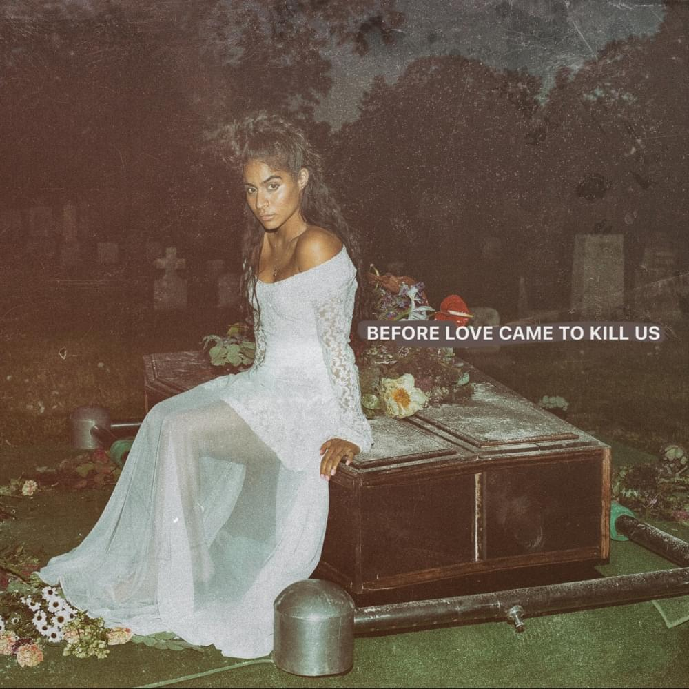 An album cover featuring a faded photograph of a woman staring at the camera wearing a white dress. She is sitting on a brown coffin covered with flowers.