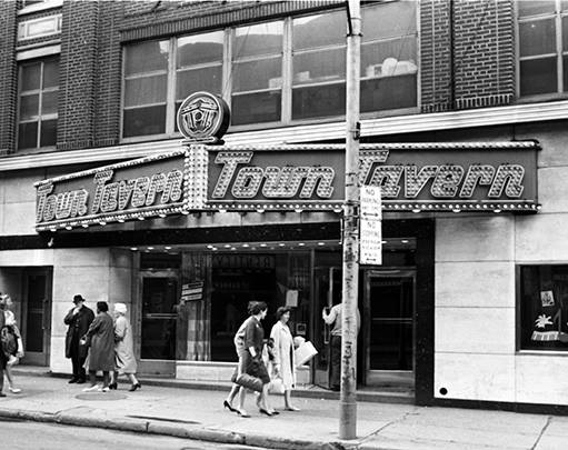 """A  black and white exterior image of a multi-storey building. A marquee outside reads """"Town Tavern"""". Men and women walk alongside the sidewalk in front of the venue."""