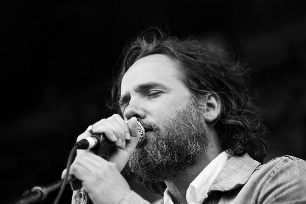 Gros plan d'un homme barbu tenant un micro avec les yeux fermés.