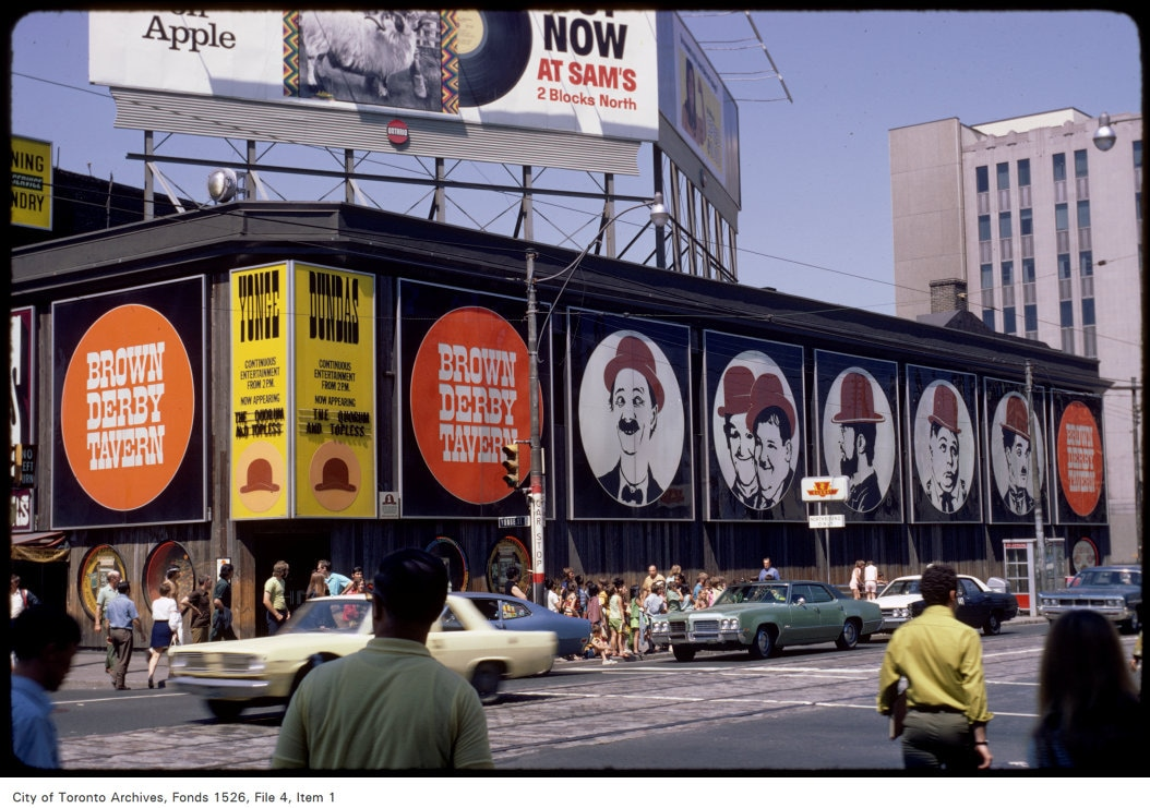 """A colour photograph of the exterior of a large building sitting on a city corner. A two-storey building, the upper story features no windows apart from large circular images of famous stars of Hollywood, such as Laurel and Hardy, all wearing brown derby hats. The corner of the building features a yellow marquee, the top of which is labelled """"Yonge"""" and """"Dundas"""" to indicate the two streets on which the building sits. Below the  marquee lists upcoming entertainment."""