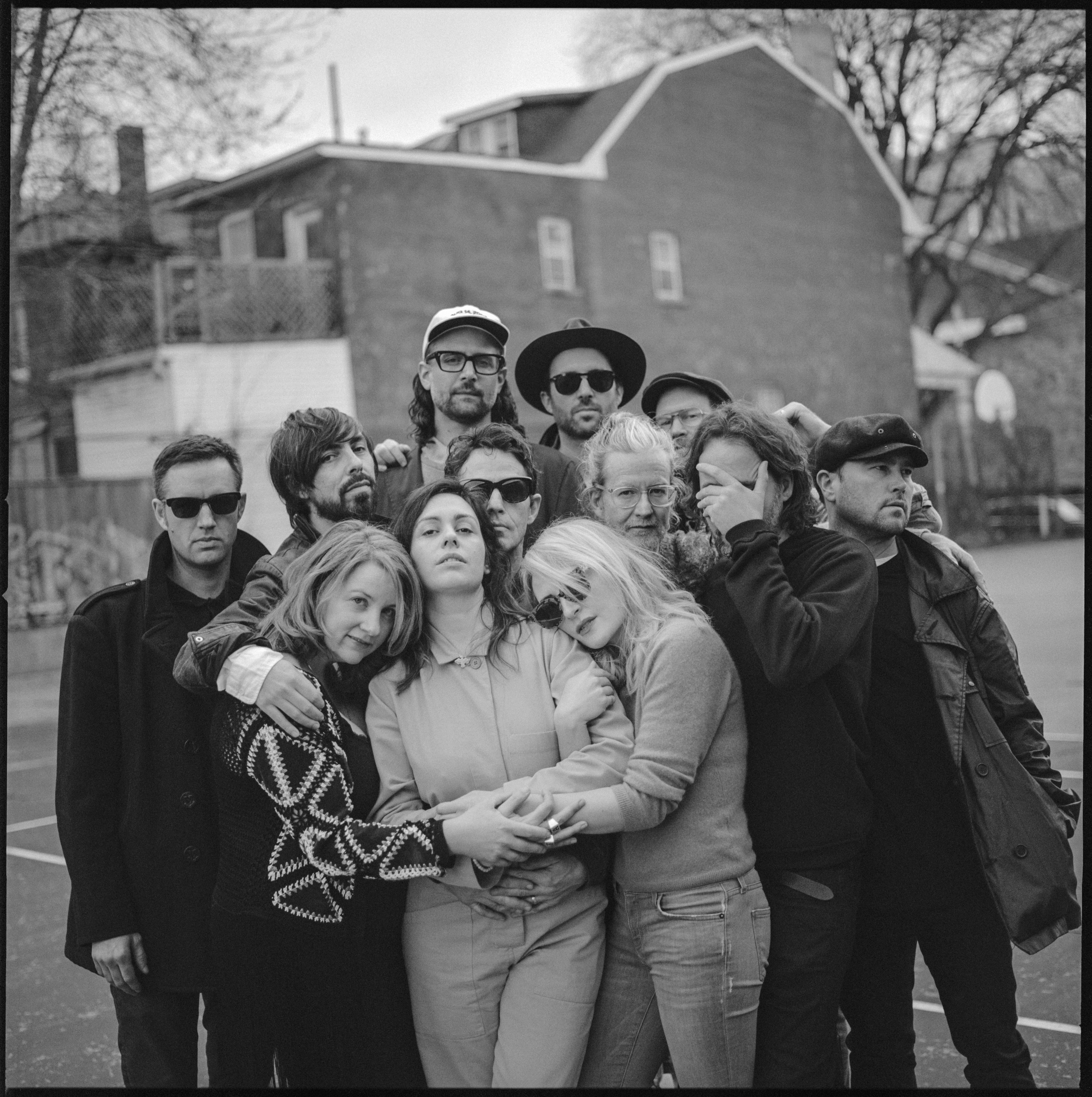 12 people huddle in a group in a black and white photograph. They stand on a children's playground, with a brick house behind them. The group is a blend of men and women. They are dressed casually but with long sleeves, as if for fall weather.