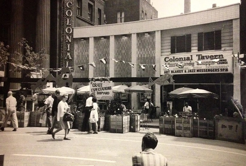 """A black and white photograph of the exterior of a two-storey building. Umbrellas and tables are set up outside with pedestrians walking in front. On the building a sign reads """"Colonial Tavern"""", below which is a marquee advertising upcoming acts, such as Art Blakey and Jazz Messengers."""