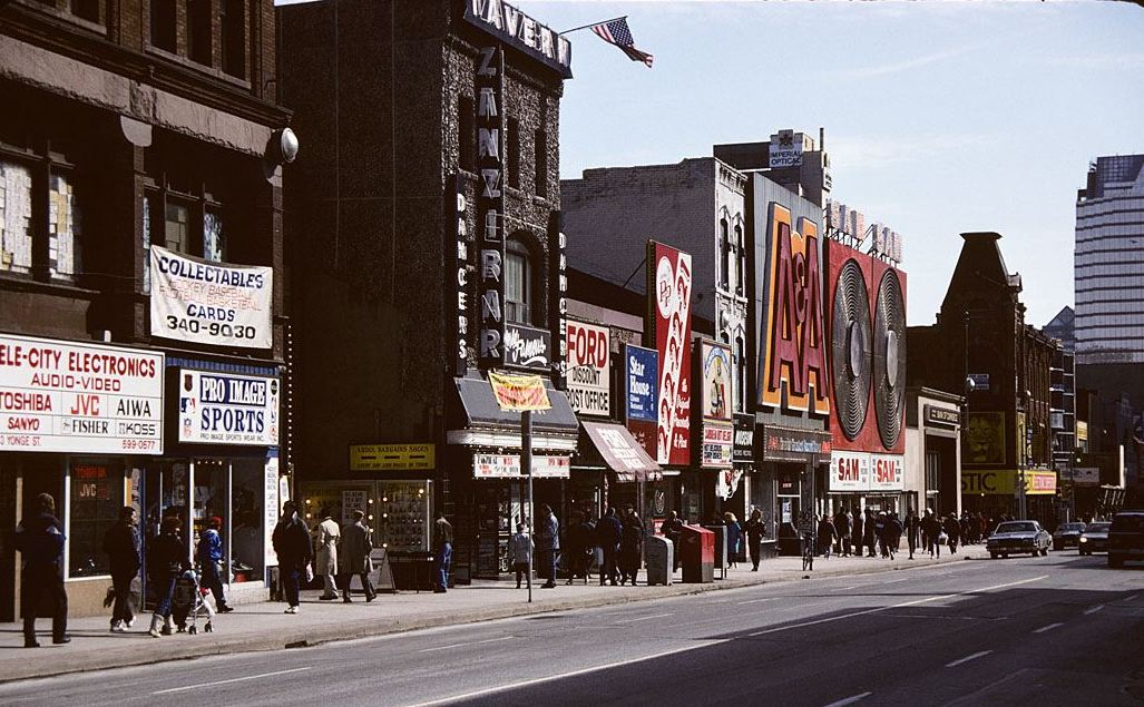 A colour photograph of a street scene from the 1970s. A line of storefronts offer electronics, sports equipment, and music. In the distance, two large record store signs can be seen: A&A and Sam the Record Man.
