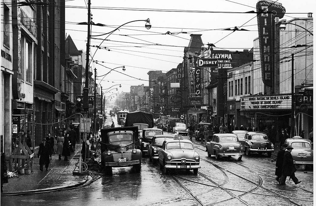 A black and white photo showing a 1950s street scene. Numerous cars drive along the main road, while on both sides of the street, large signs advertise shops, bars, and theatres.