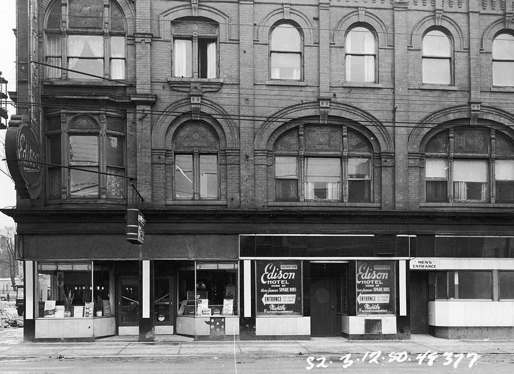 """A black and white photograph of an exterior of a multi-storey building. The main level advertises the """"Edison Hotel"""" in its storefront window."""