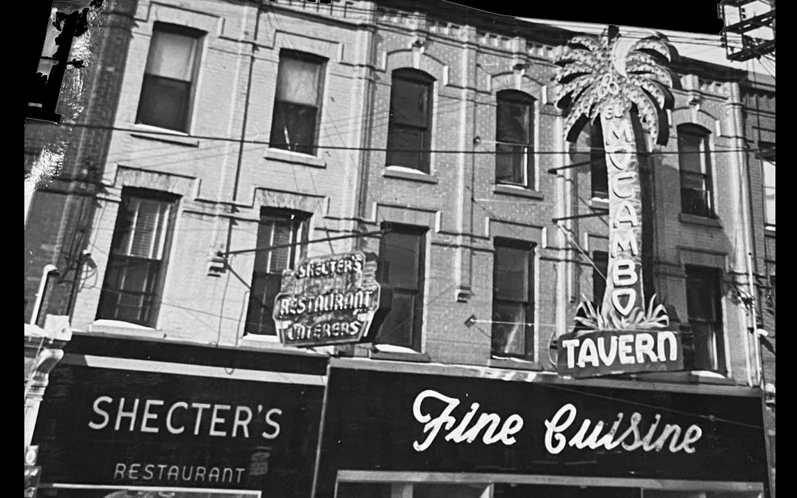 "A black and white image showing a Toronto city block. On the right is a building featuring a neon sign in the shape of a palm tree that reads ""El Mocambo Tavern"". Below reads ""Fine Cuisine"""