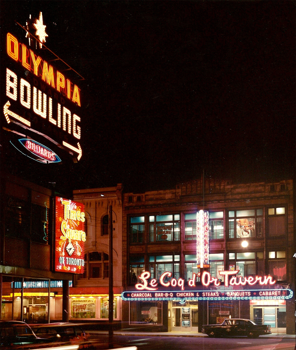 """A colour photograph showing the exterior of a building on which """"Le Coq d'Or Tavern"""" is lit in bright red and white lights outside the first floor. A smaller neon sign on the opposite side of the road advertises """"Times Square of Toronto"""". Above it, a large neon sign reads """"Olympia Bowling"""" with arrows pointing in either direction."""