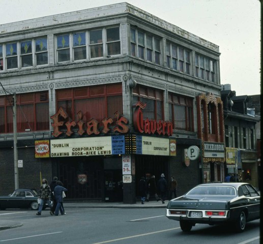 """A colour photograph of the exterior of a three-storey building. Large letters above the main floor of the building in red advertise """"Friar's Tavern."""" Underneath the large sign is a marquee advertising upcoming bands."""
