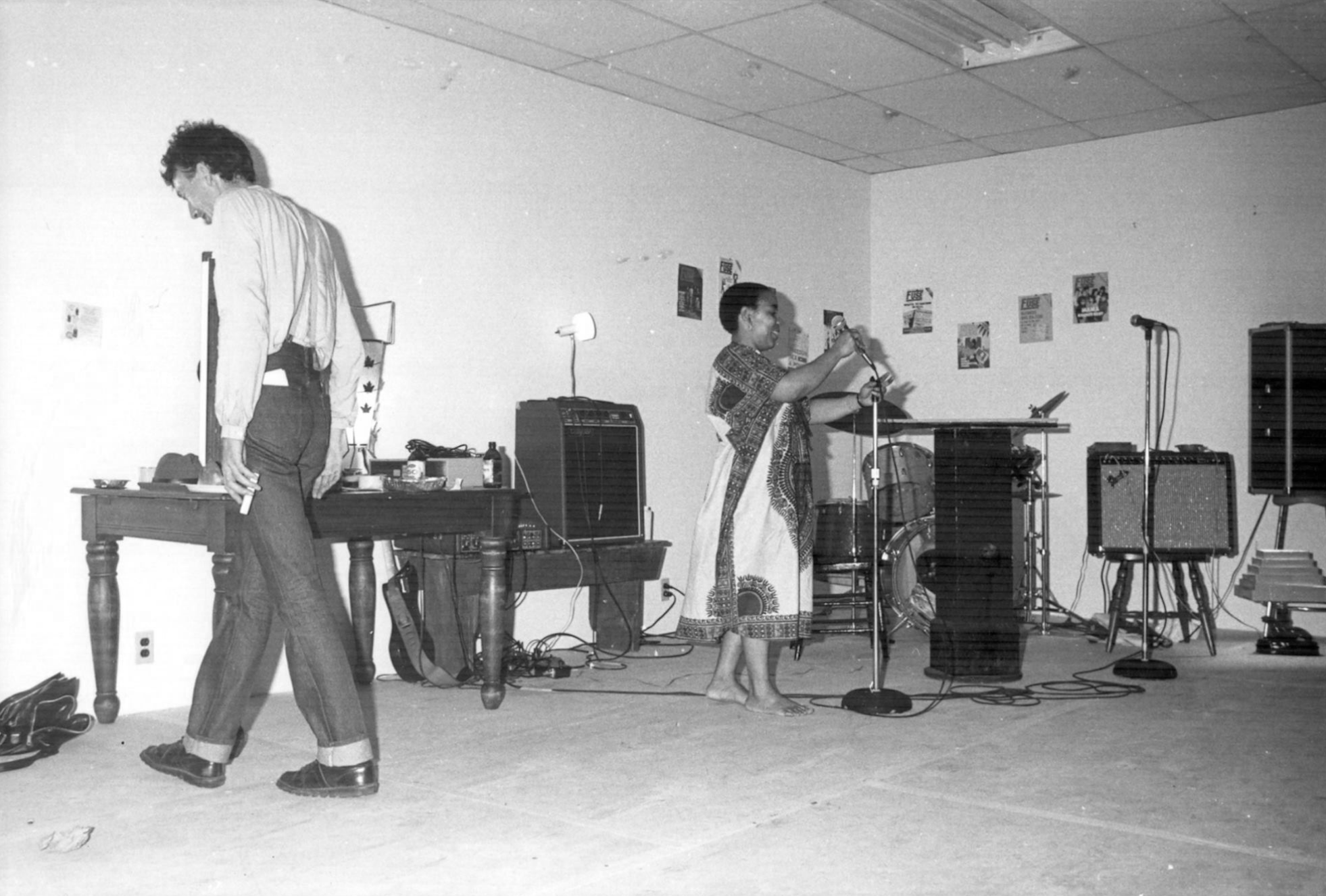 A black and white image of a room with two people standing in it. One faces a wall to the left of a wooden table. The other, a woman, holds a microphone stand. Other microphones and speaker equipment are also in the room nearby.
