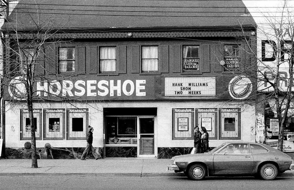 An exterior black and white photo of a two-story building. A large sign affixed to the left-hand side of the building reads: Horseshoe. On the right, a marquee announces upcoming acts of Hank Williams Show Two Weeks. A 1970s-era car is parked out front. Photo by Patrick Cummins.