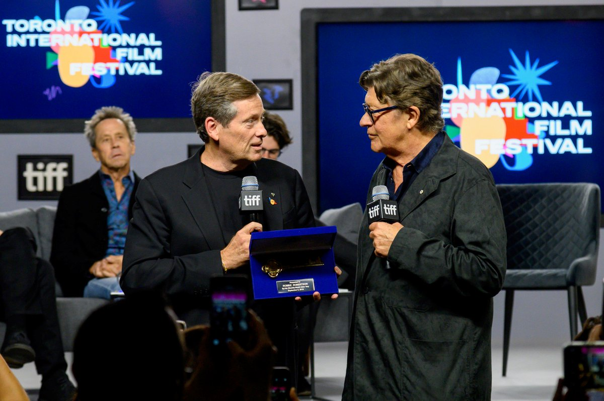 A colour photograph of two men, both wearing black and holding microphones. The man on the left holds a ceremonial box with a key inside, handing it to the man on the right.