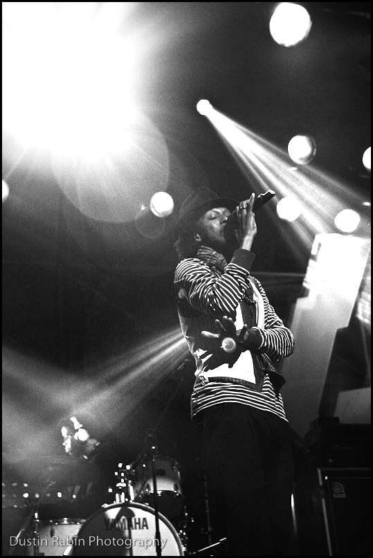 Black and white photograph of black man wearing dark pants, a stripe shirt and a hat singing into a microphone with bright stage lights shining in the background. A drummer and his drum set are in the bottom left corner.