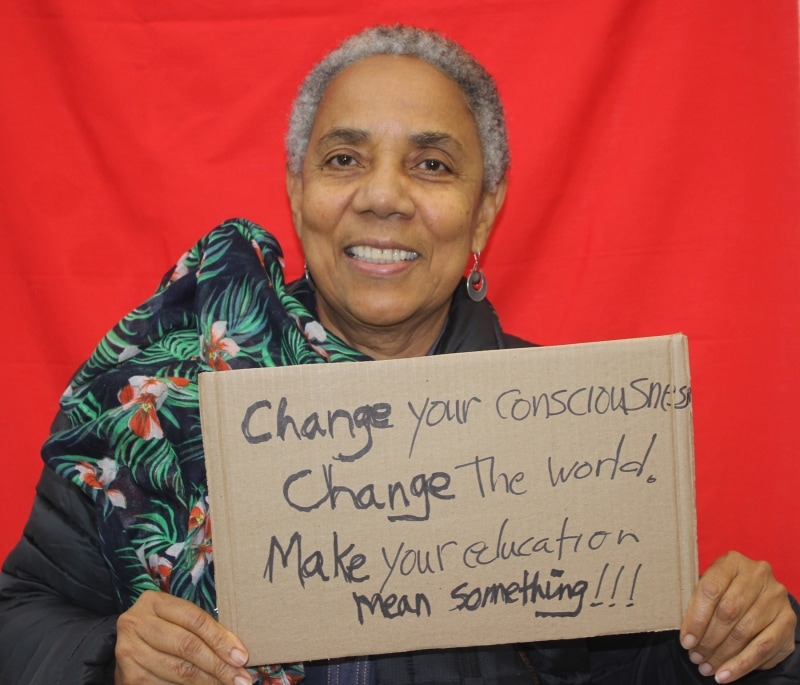 """A woman is in front of a red backdrop. She wears a floral scarf and holds up a sign made of cardboard on which is written in black ink """"Change your consciousness, Change the world. Make your education mean something!!!"""""""