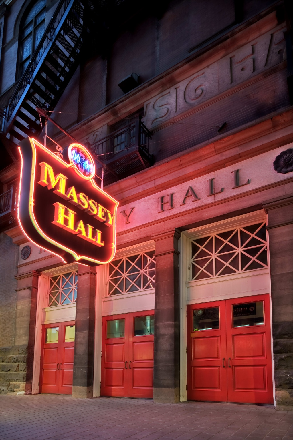 An exterior image of Massey Hall in colour, featuring its iconic neon signage and three bright red doors.