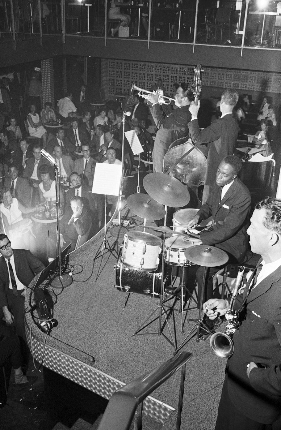 A black and white photograph showing the interior of a packed music venue. On stage a group of musicians play, including a trumpeter, a bass player, and a drummer. The audience, seated below them and on a higher second level, look on.