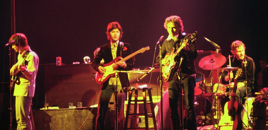 Four men stand on stage dressed in 1970s clothes. One holds a guitar and stands in front of a microphone. To his left two men hold and play guitars. On the far right, a man sits at a drum kit playing.