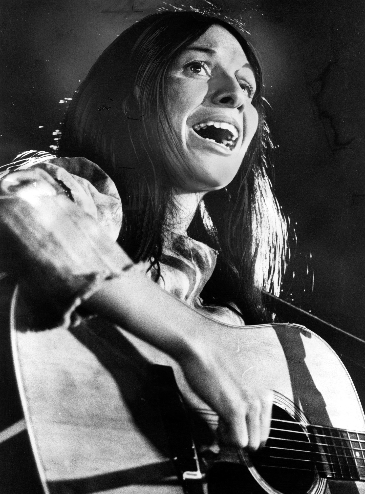 A black and white photograph of a woman with long dark hair singing into a microphone with a guitar.