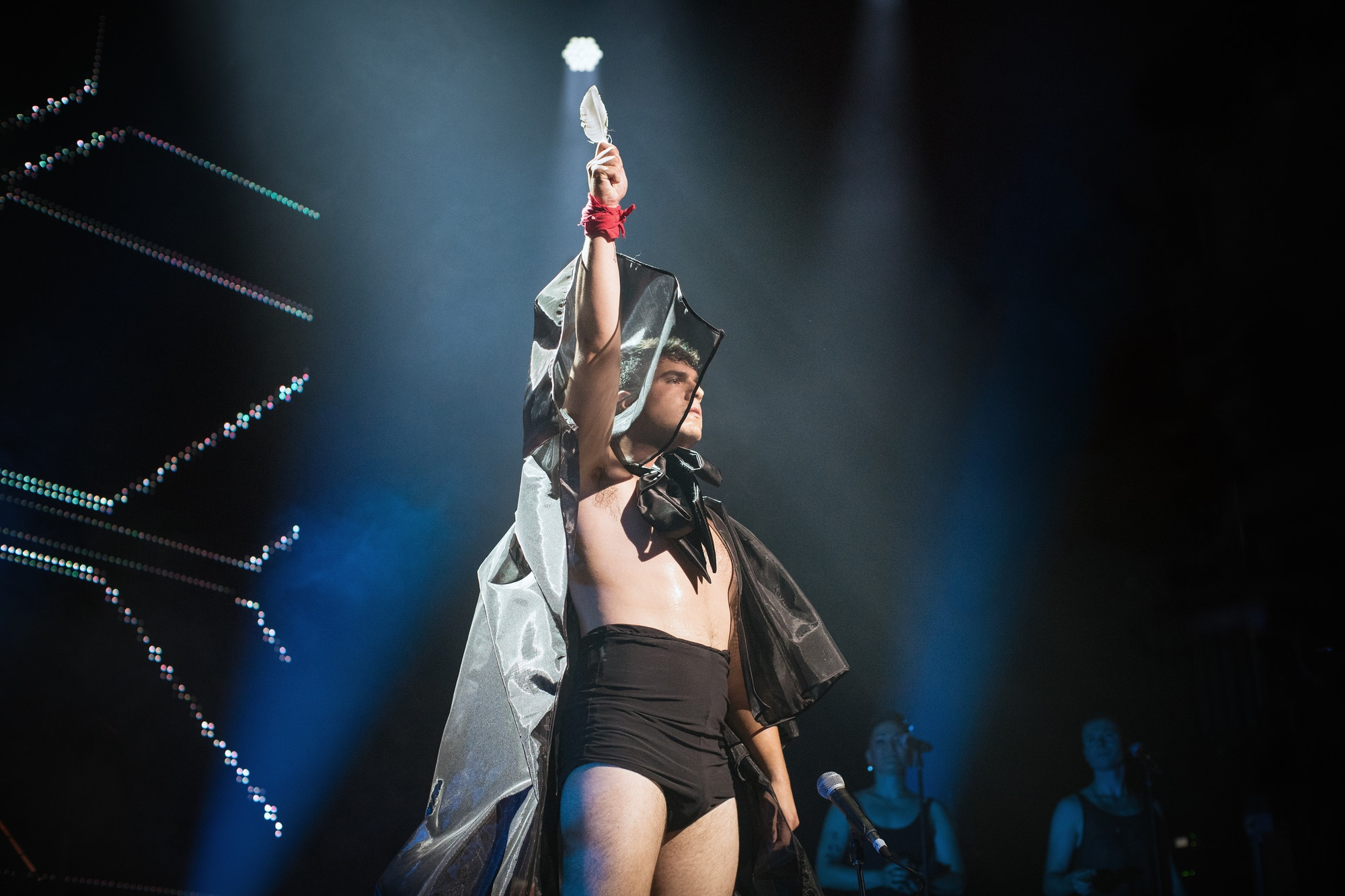 On stage a man with right arm extended upwards holds an eagle feather. On his wrist a red cloth is wrapped and tied. He is wearing a black cape and black high shorts. In front of him is a microphone and behind him to his left are two female singer