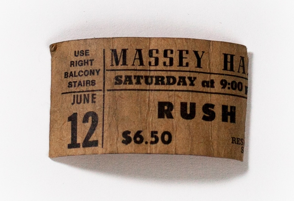 """A colour photograph of a browning ticket stub. On the left of the ticket it reads: """"Use right balcony stairs. June 12"""". The right portion of the ticket reads: """"Massey Hall, Saturday at 9:00pm, RUSH, $6.50"""""""