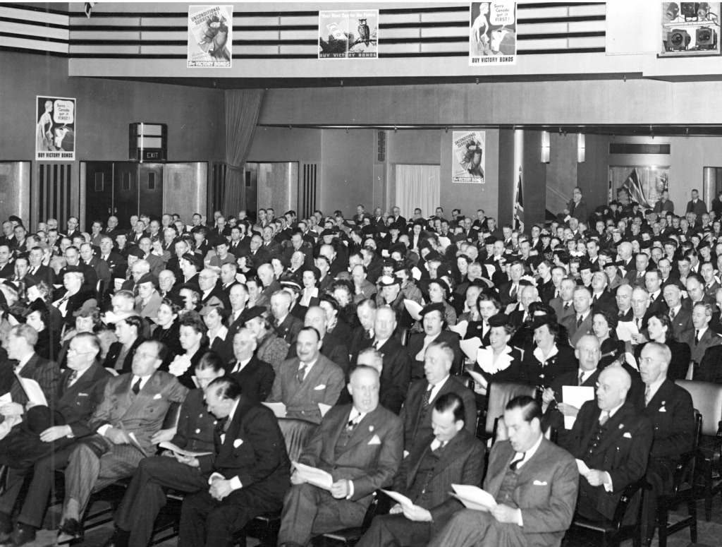 Black and white photo of an audience sitting in a theatre featuring Art Deco decoration. Every seat is full. Photo dates to 1943.