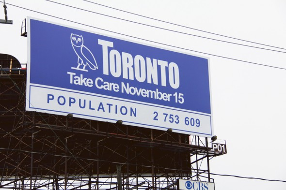 An exterior photograph of a billboard above a city highway. The words Toronto and Take Care November 15 are written in white and are to the right of a stylized image of an owl against a blue background. Below, in blue, is written Population 2 753 609.