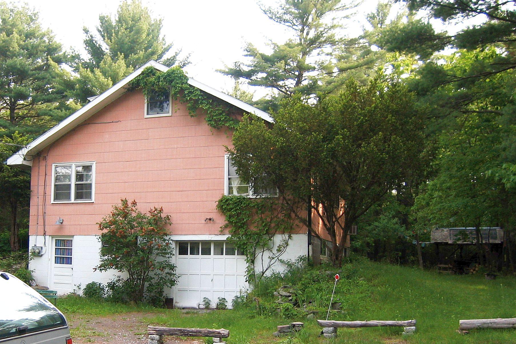 Une photographie d'une maison à plusieurs étages. La partie supérieure est peinte en rose clair. Le bas, y compris le garage, est peint en blanc. Elle se trouve dans un cadre rural, entourée d'arbres.
