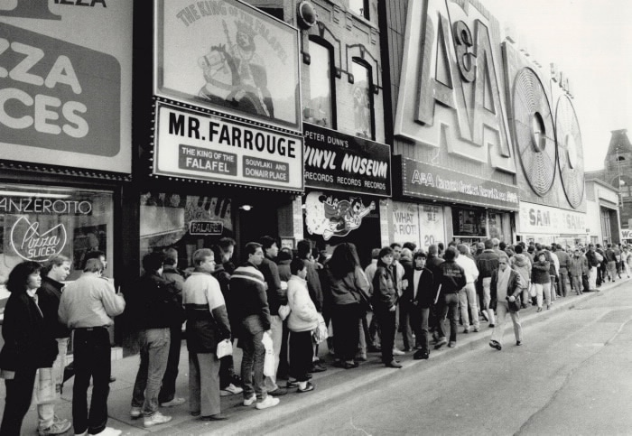 "A black and white image of a busy street scene with dozens of people lined up on the sidewalk outside storefronts with exterior signage advertising ""Mr Farrouge: the King of Falafel"" ""Peter Dunn's Vinyl Museum"", """"AAA, Canada's Greatest Record Store"", and ""Sam the Record Man"". Photo by Dale Brazao, 1987. Courtesy of the Toronto Star Archives"