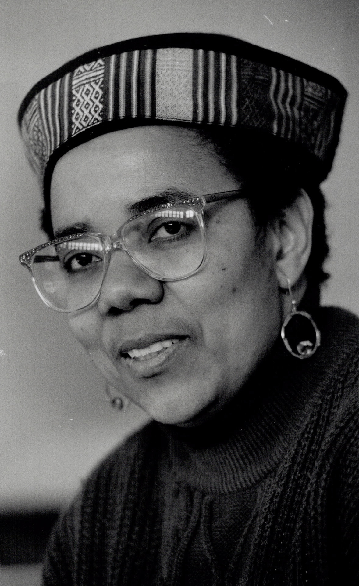 A black and white photo portrait of the head and shoulders of a woman. She looks at the camera. She is wearing a turtleneck sweater, an African-styled short cap, glasses, as well as dangly earrings.