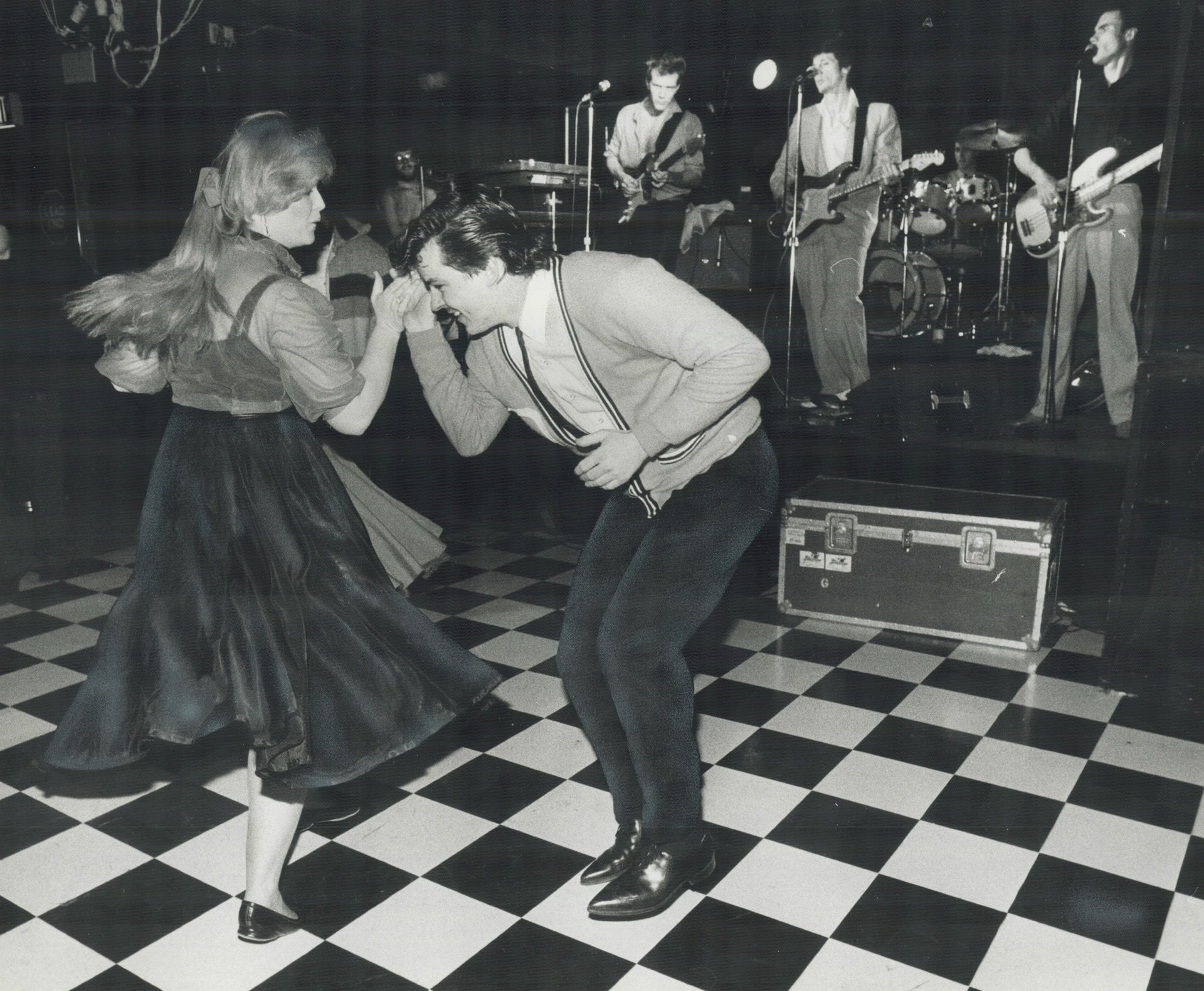 A couple dance on a checkboard floor while a band plays on stage. They are wearing 1950s style clothing, including a poodle skirt and cardigan.