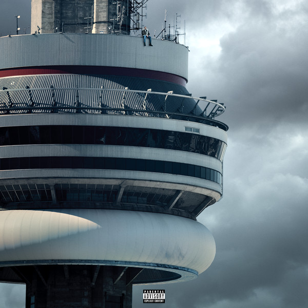 A colour photo showing the top of a large structure: Toronto's CN Tower. At the very top, seated outside, is a man wearing jeans and a jacket.