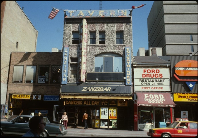 """A colour photograph of the exterior of a building with a stone facade. It sits amongst other buildings on a bustling city street. Signs outside the building advertise the Zanzibar as well as """"Dancers All Day"""""""