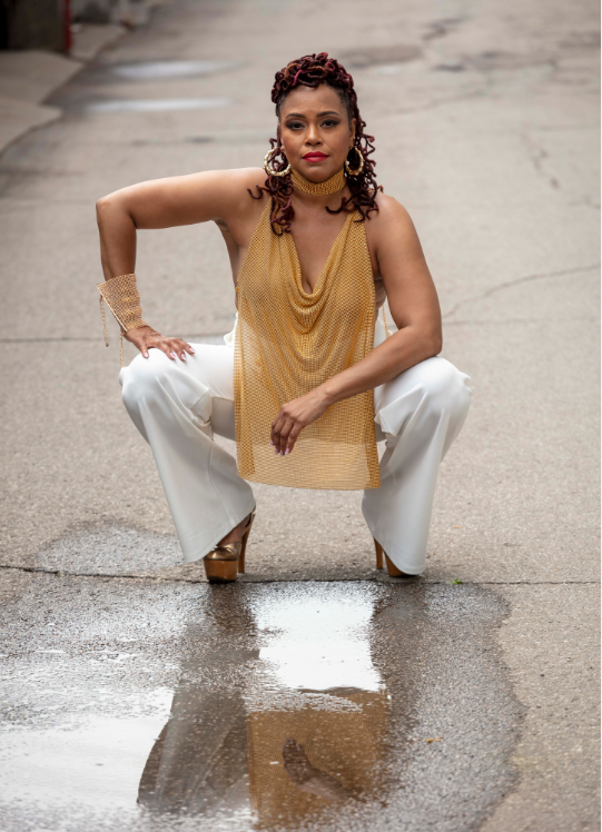 A woman in a gold top and white pants crouches outside.