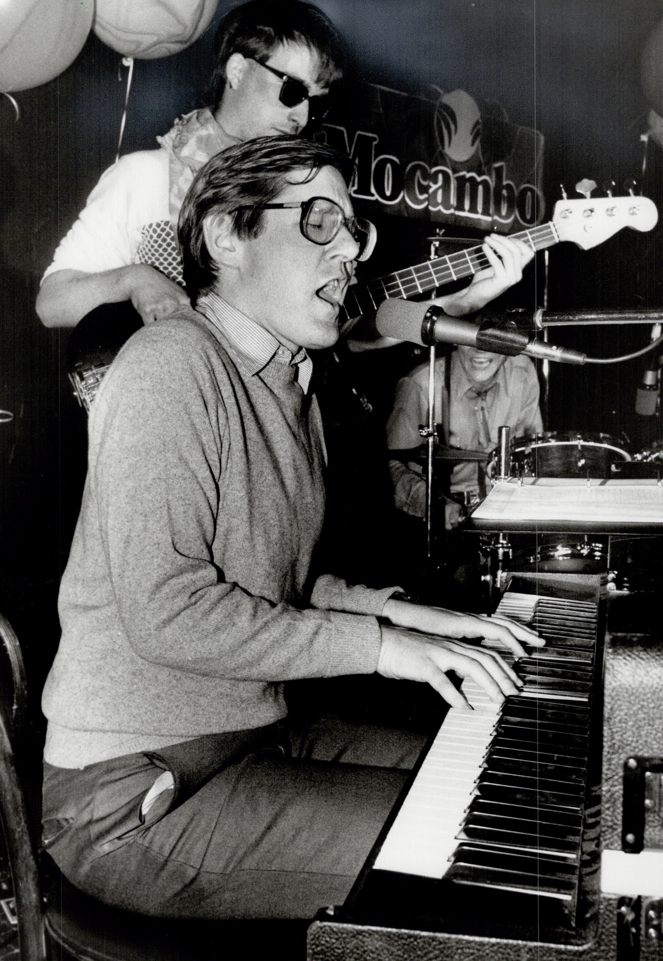 A middle-aged man is seated at a keyboard singing into a microphone. He is wearing a collared shirt and sweater. Behind him, a man with sunglasses plays guitar.