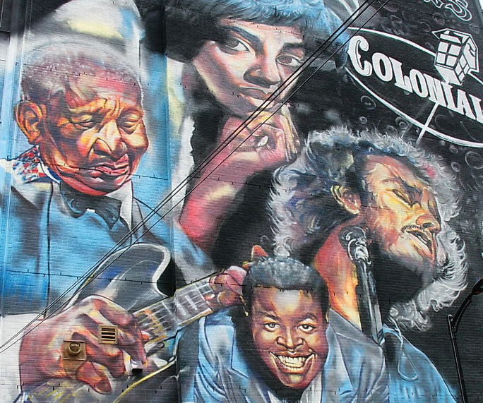 A multi-storey mural painted on the exterior of the building, featuring a combination of musician portraits and iconic signage.