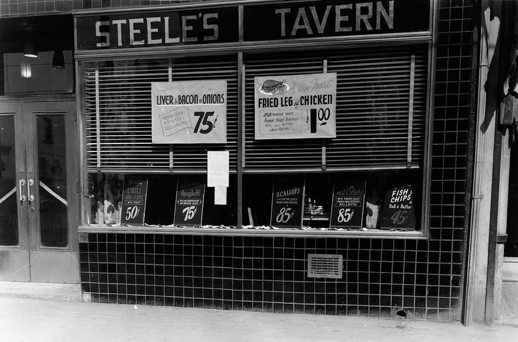 A black and white photograph showing the exterior of a restaurant storefront. Above large, plate-glass windows is a sign reading Steele's Tavern. In the windows are paper advertisements for meal specials: liver, bacon, and onions for 75 cents as well as fried leg of chicken for one dollar.