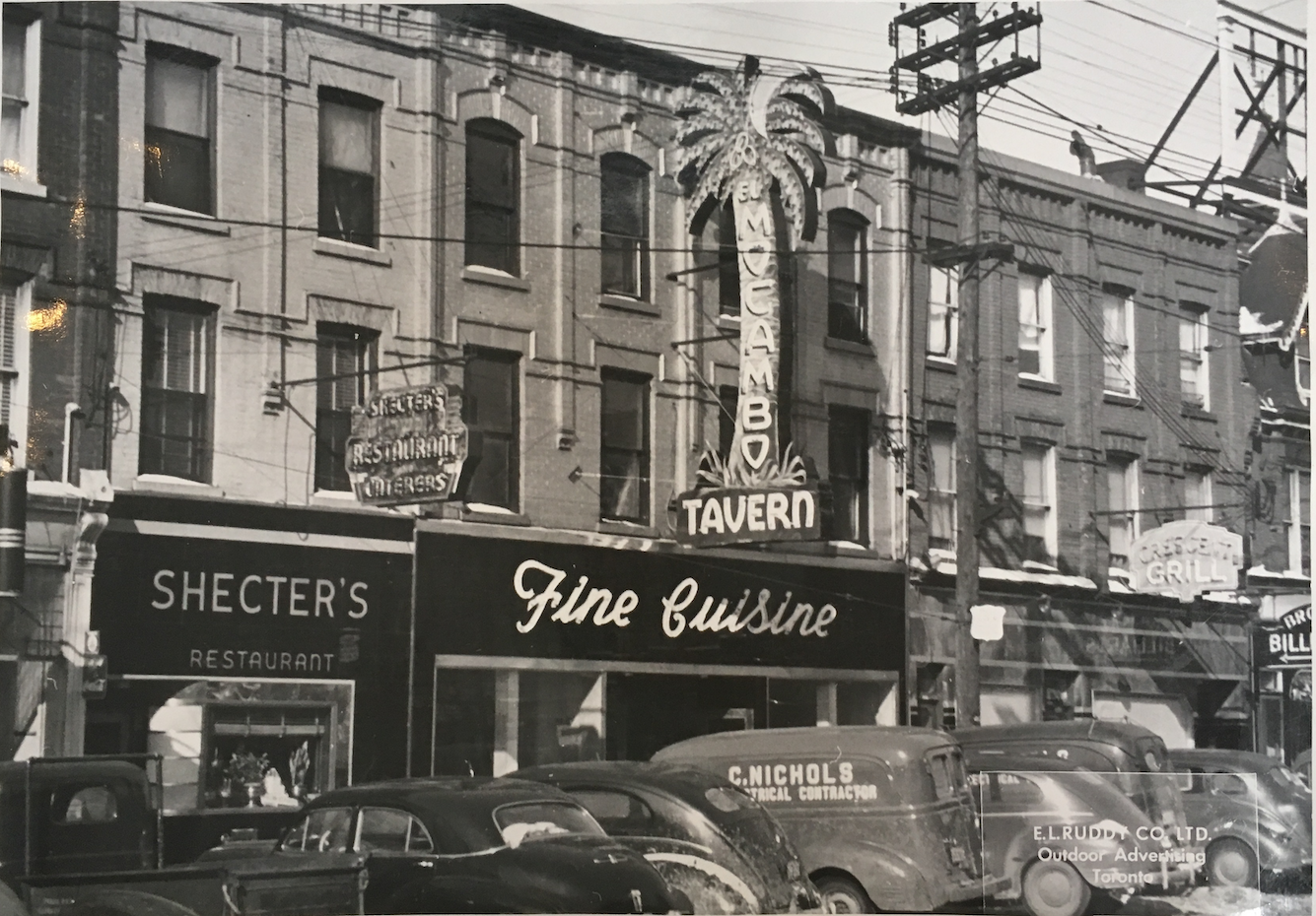 """A black and white image showing a Toronto city block. On the right is a building featuring a neon sign in the shape of a palm tree that reads """"El Mocambo Tavern"""". Below reads """"Fine Cuisine"""""""